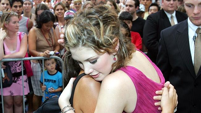 Group hug ... Delta Goodrem with Queensland fan Sami Stockton in 2005. Pic Annette Dew