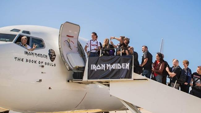 Let's rock: Bruce Dickinson gives Iron Maiden fans the metal sign before flying them to P